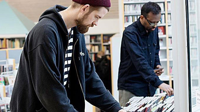 Men browsing CD-records in library.