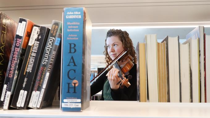 Woman playing the violin in the library.